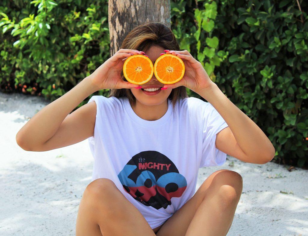 Imagem de uma jovem segurando duas rodelas de laranja em frente aos olhos.