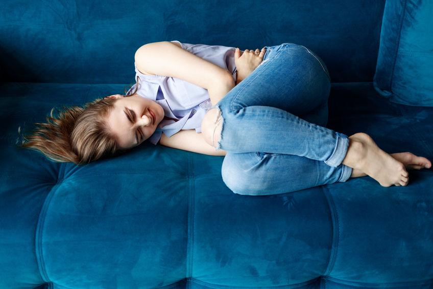 Mulher jovem e bonita sente raiva e dor da menstruação. Deitada e sofrendo no sofá.