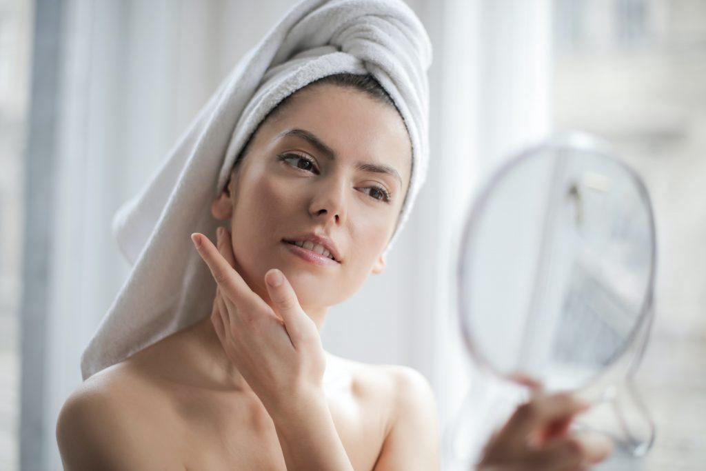 Imagem de uma mulher olhando no espelho.