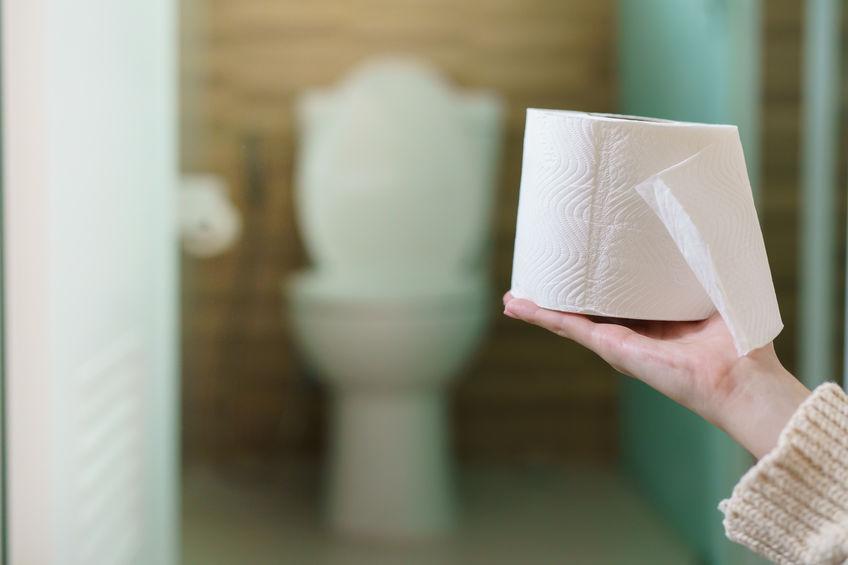 Mulher segurando rolo de papel higiênico na frente do banheiro.