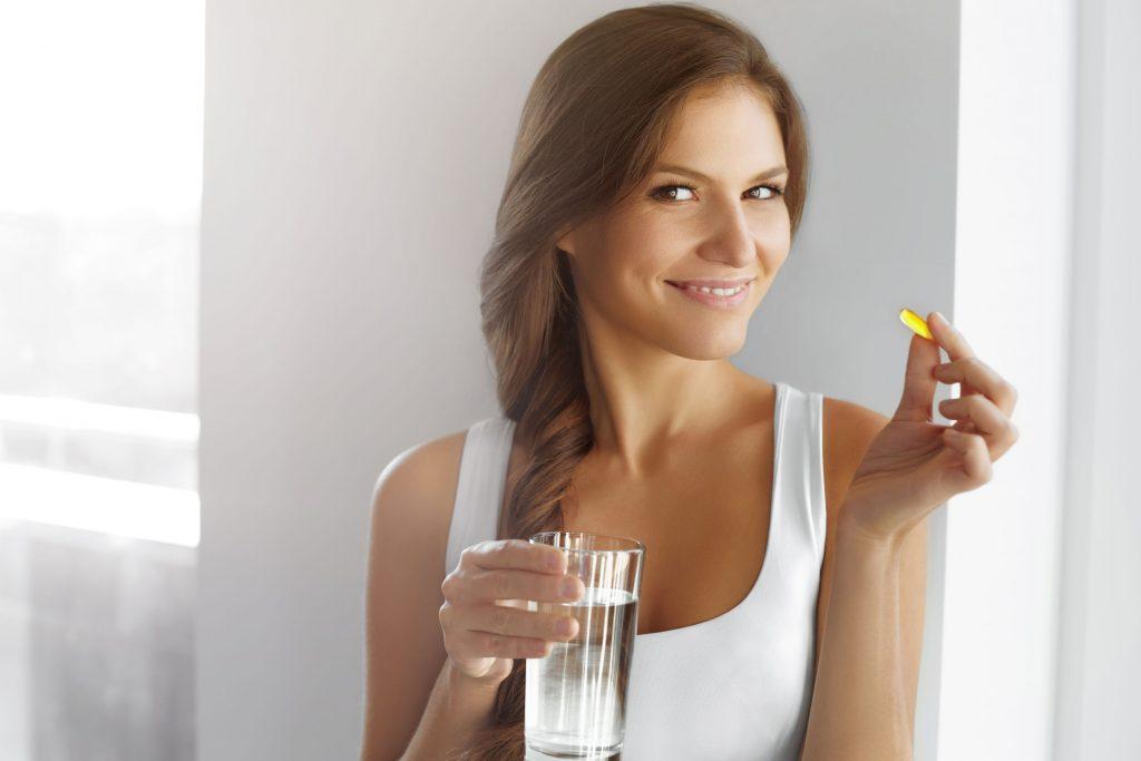 Mulher segurando cápsula de suplemento.