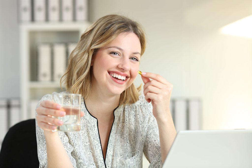 Imagem de uma mulher tomando uma cápsula de vitamina E.