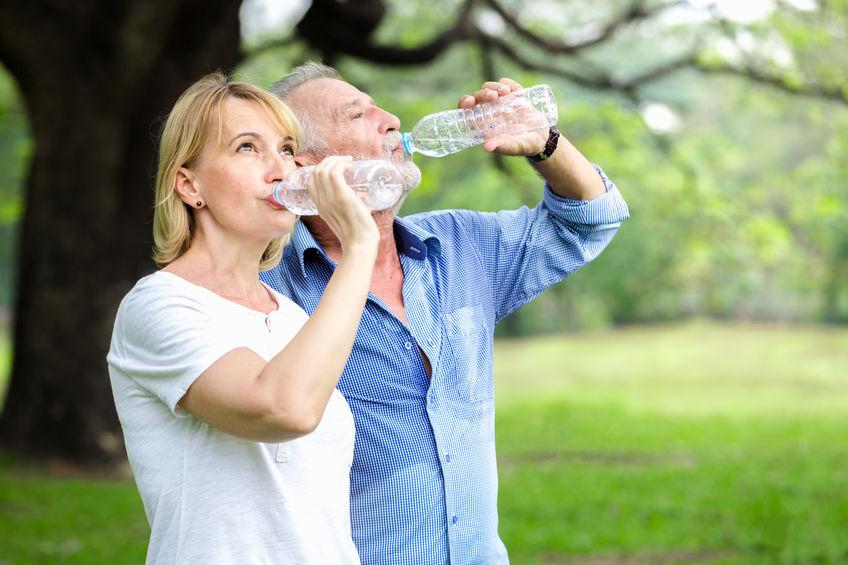 Retrato de casal sênior em pé de água potável no parque