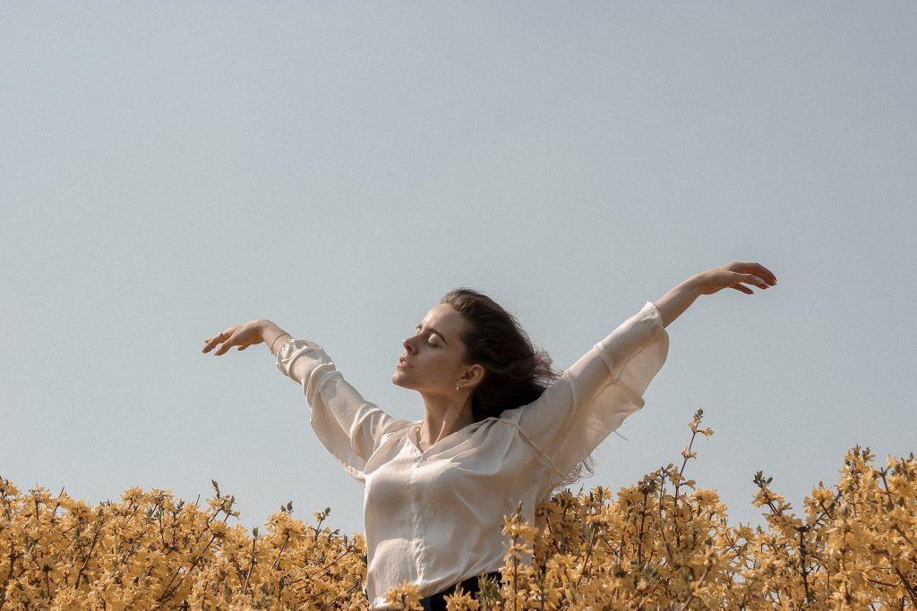 Imagem de uma mulher com os braços abertos.