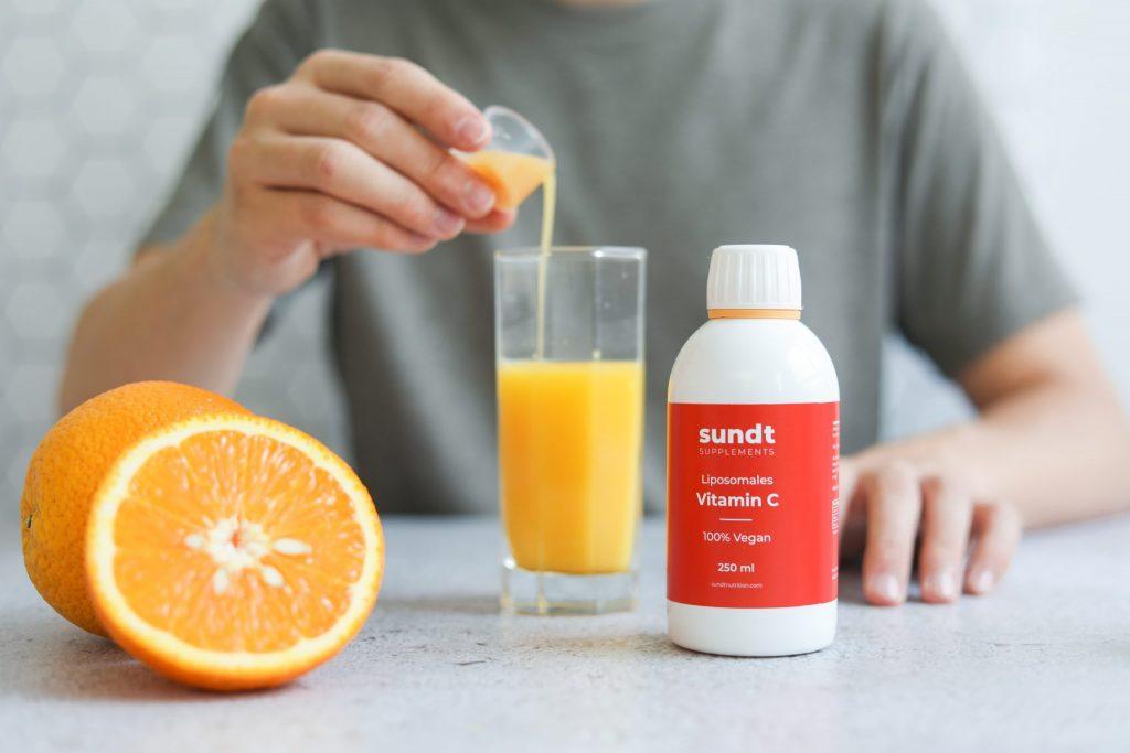 Imagem de um homem tomando um suplemento de vitamina C.