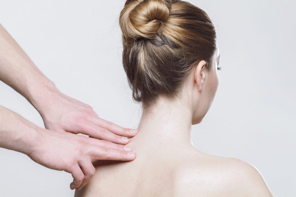 Imagem de uma pessoa massageando os ombros de uma mulher.