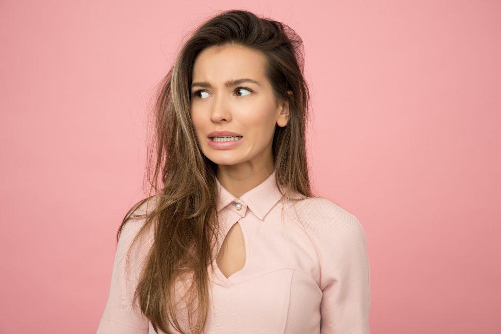 mulher com fundo rosa na parede