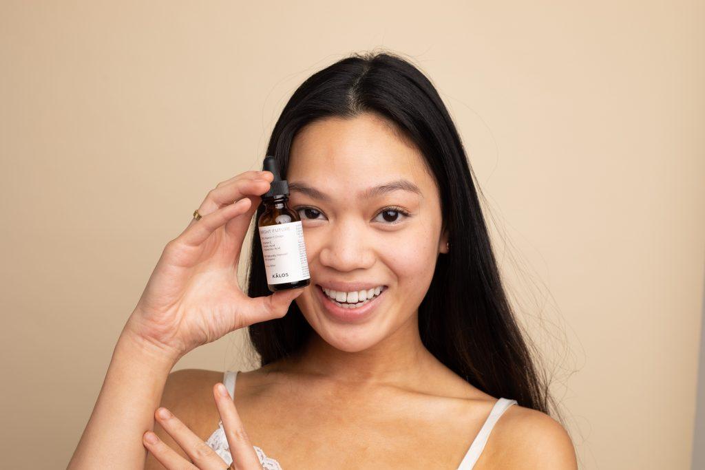Imagem de uma mulher segurando um frasco de sérum de vitamina C.