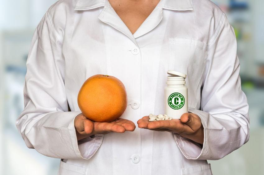 Médica de jaleco segurando uma laranja e suplemento de vitamina.