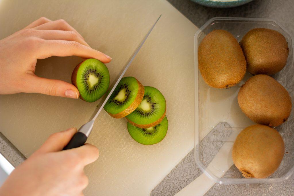 Imagem de uma mulher cortando rodelas de Kiwi.